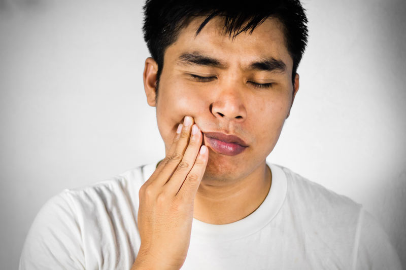 asian man having tooth pain and needs a root canal